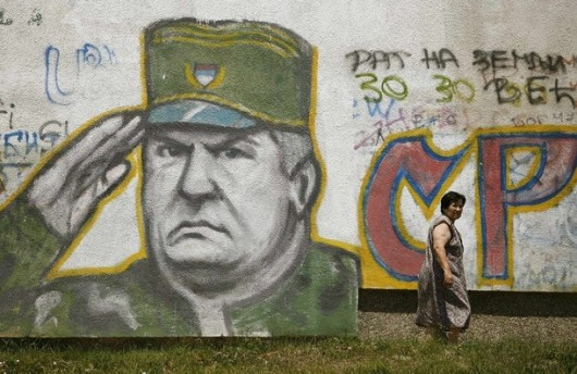 A woman walks past graffiti of Bosnian Serb fugitive general Ratko Mladic in Belgrade